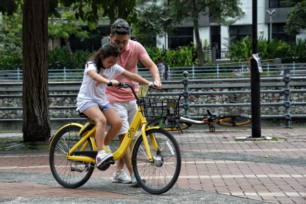 little girl getting taught how to ride a bike from father