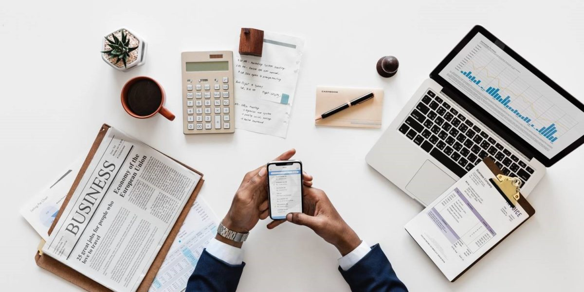 Business papers on a desk in front of a man looking at a cell phone